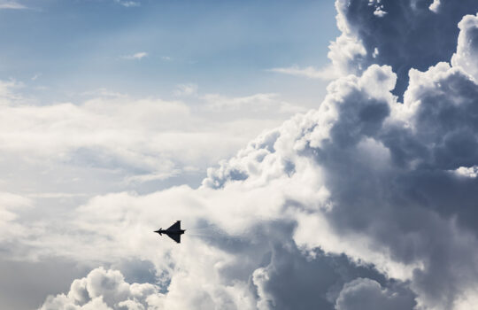 jet fighter aircraft silhouetted against a cloudy sky