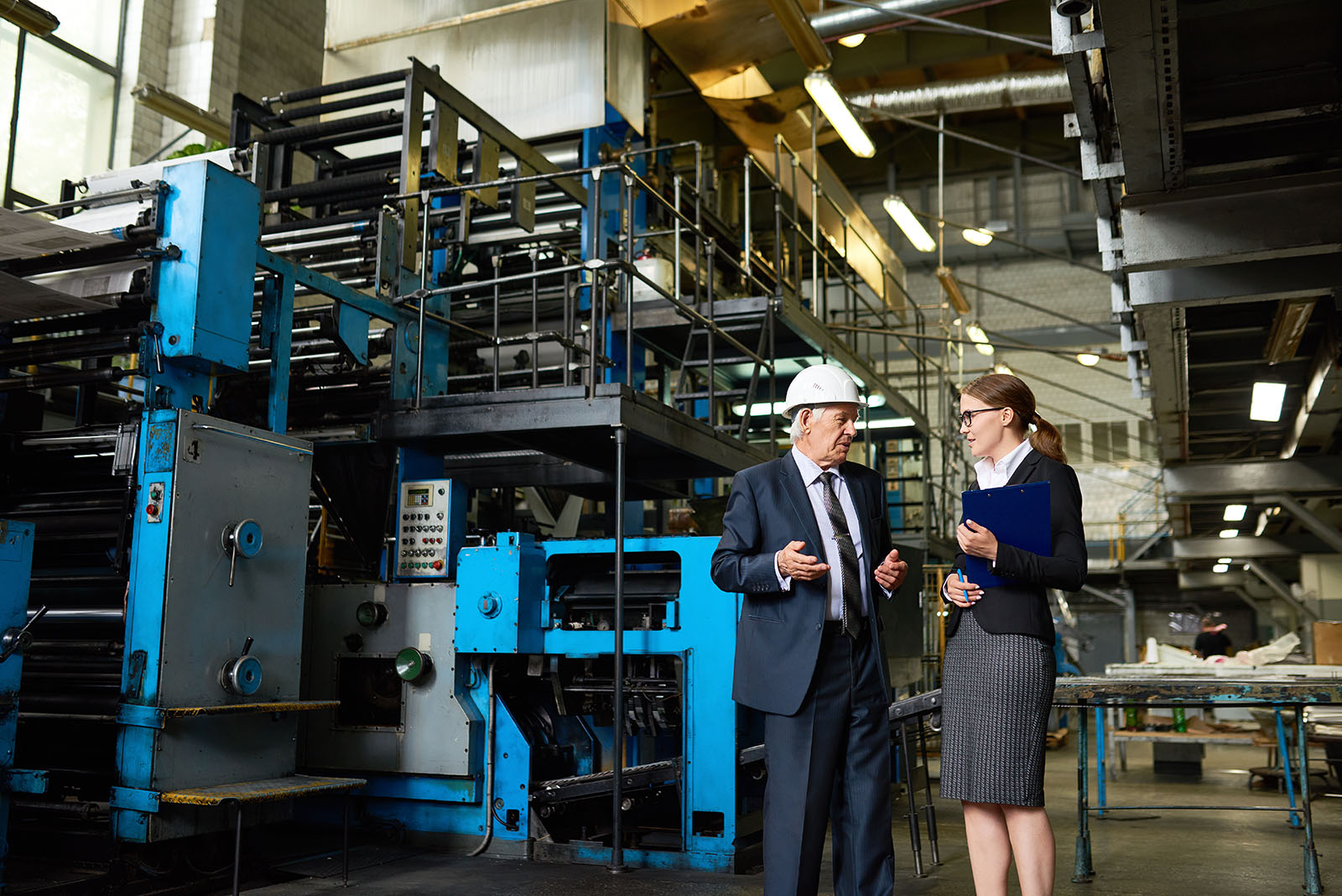 Portrait of senior businessman wearing hardhat talking to assistant manager in modern factory workshop