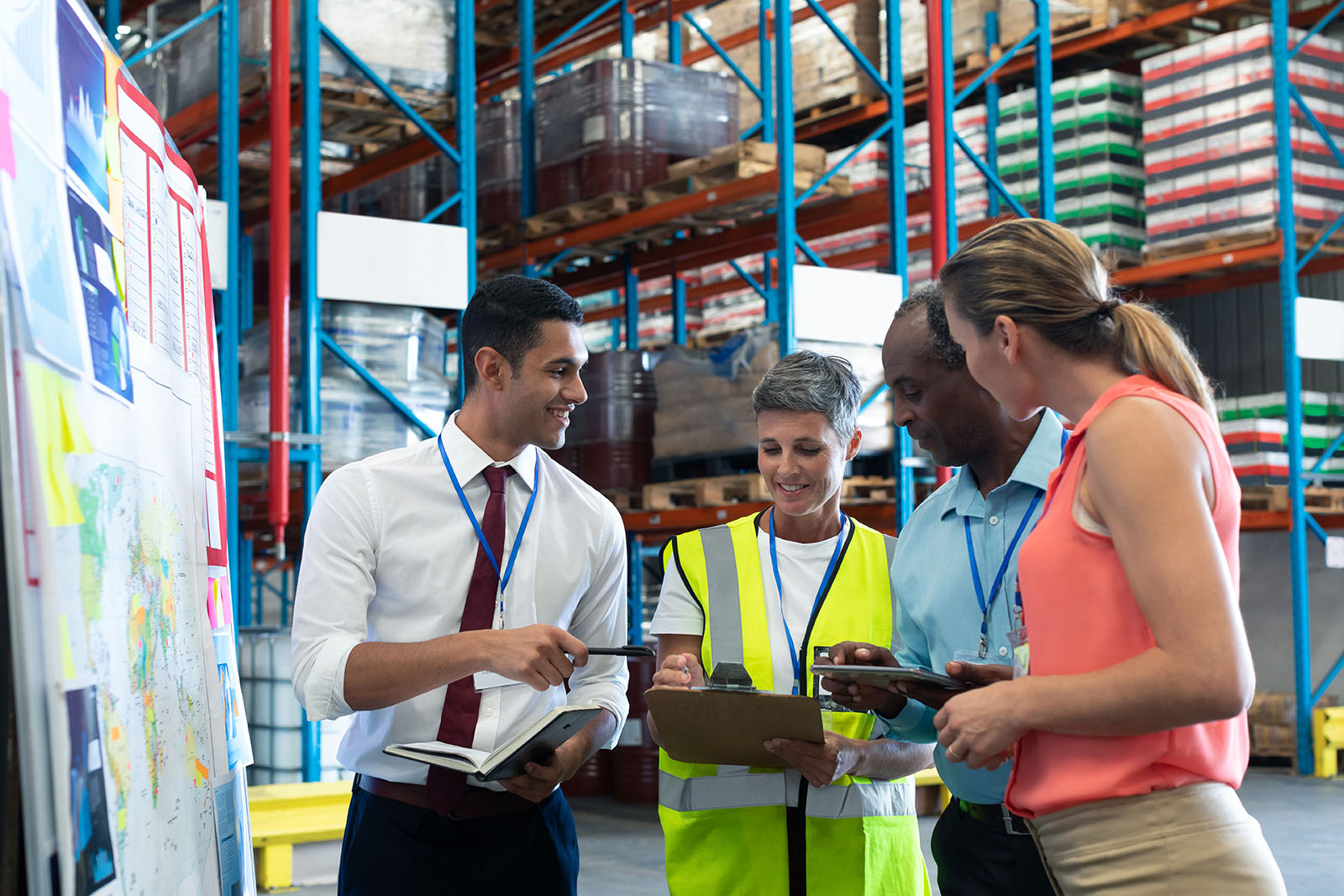 Group of people standing in the middle of a logistics warehouse receiving advice on their facilities management