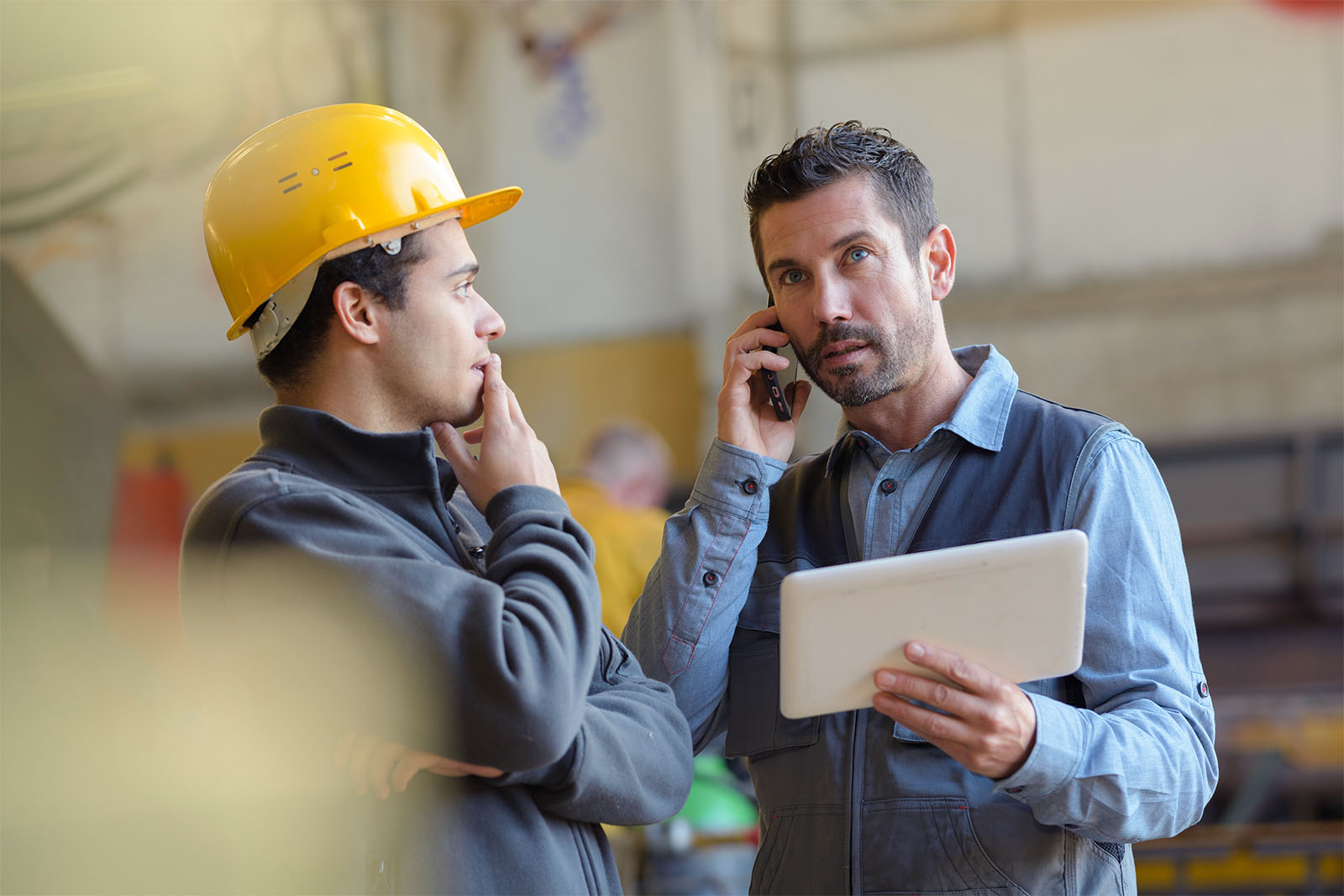 Male client conducting a call alongside an engineer in a hard hat