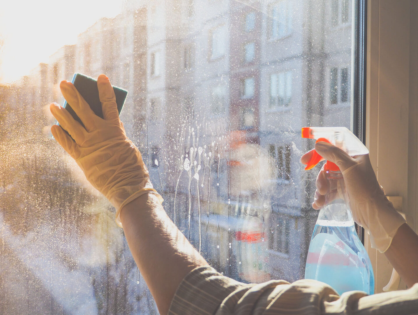 Close up of a cleaner washing windows with a spray bottle