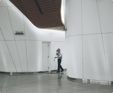 Long shot of a cleaner sweeping a hallway