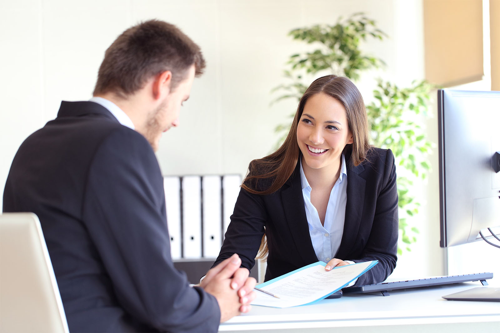 A customer service assistant advising a client at her desk